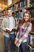 Classmates standing in library smiling at camera in college
