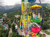 Family of three having fun on the ferris wheel against the mountains and sky with clouds, view from