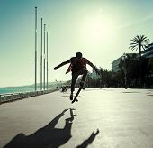 pic of skateboarding  - Silhouette of Skateboarder jumping in city on background of promenade and sea - JPG