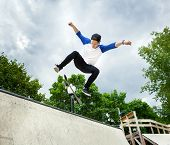 stock photo of skateboard  - Skateboarder jumping in halfpipe at skatepark on background sky cloudy - JPG