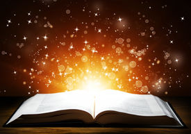 pic of xmas star  - Old open book with magic light and falling stars on wooden table - JPG