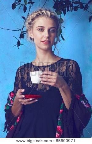 Young beautiful woman with blond hair in braids romantic hairstyle enjoying cup of coffee against blue painted grunge wall