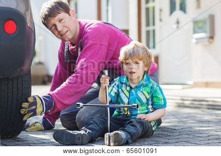 Father And Adorable Little Boy Repairing Car And Changing Wheel Together