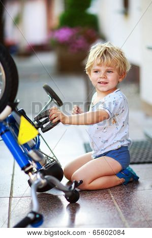 Happy Funny Toddler Boy Of Two Years Repairing His First Bike