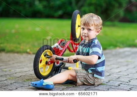 Happy Funny Toddler Boy Of Three Years Repairing His First Bike
