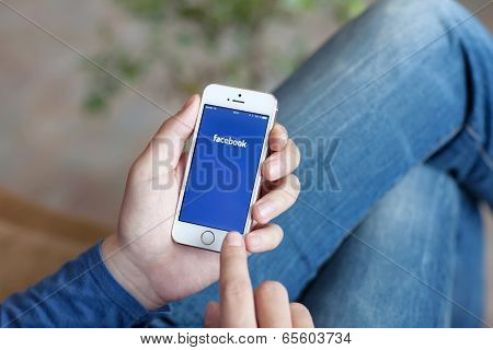 Man Holding A White Iphone With App Facebook On The Screen