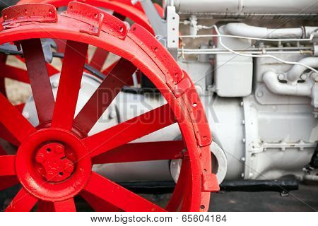Fragment Of Old White Tractor With Red Wheel