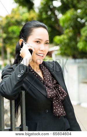Real estate - Young Indonesian realtor showing an house or apartment, it could be the landlord too, she has a customer conversation with a prospective customer on the mobile phone