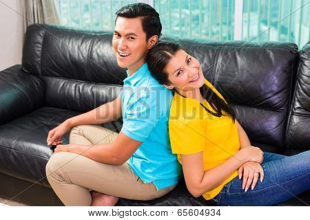 Young Asian handsome couple having long-term relationship sitting on sofa or couch