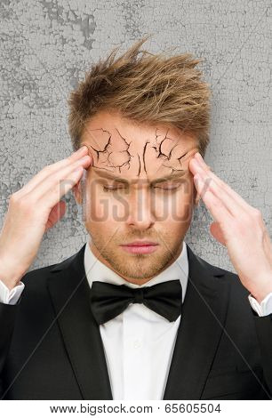 Portrait of business man with closed eyes putting hands on peeling off and cracked forehead, isolated on white. Concept of headache, high temperature and aging