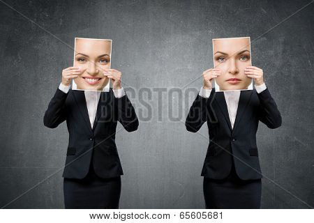 Portrait of young business woman hiding her mood under masks with different emotions