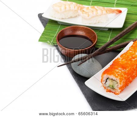 Sushi maki and shrimp sushi on black stone. Isolated on white background with copy space