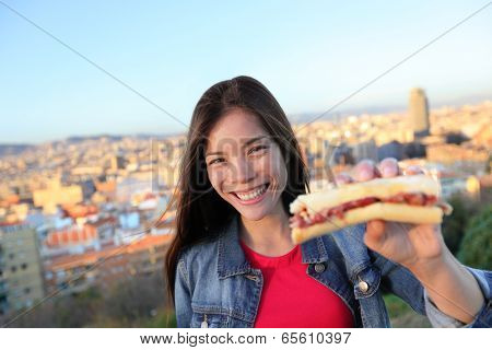 Jamon Serrano Sandwich. Woman eating in Barcelona, Spain showing traditional Spanish food, cured Iberico ham. Focus on girl, Barcelona skyline in background.