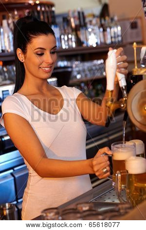 Portrait of attractive female bartender tapping beer in bar, smiling.