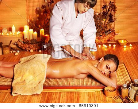 Therapist man giving Thai stretching massage to woman.