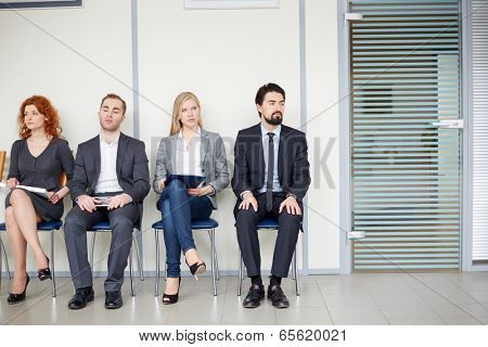 Portrait of several business associates sitting on chairs by office door