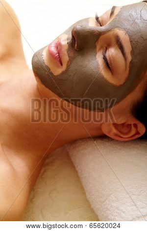 Relaxed girl with clay or mud mask on face for pore cleaning