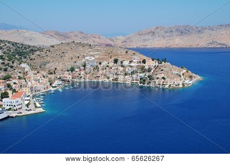 SYMI, GREECE - JUNE 19, 2011: Looking down onto Yialos harbour on the Greek island of Symi. The island is a popular destination for day trippers from Rhodes and nearby Turkey.