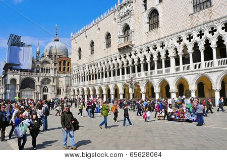 VENICE, ITALY - APRIL 12: A crowd in Piazzetta San Marco around the Palazzo Ducale and the Basilica di San Marco on April 12, 2013 in Venice, Italy. The city receives 18 million tourists per year