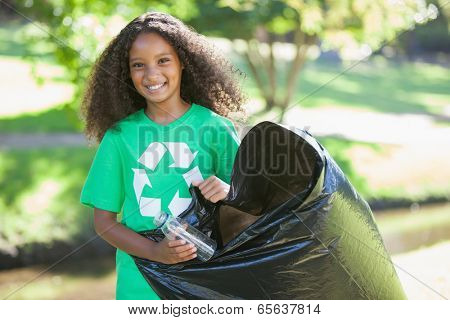 Young environmental activist smiling at the camera picking up trash on a sunny day
