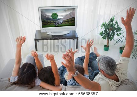 Family cheering and watching the tv at home in the living room