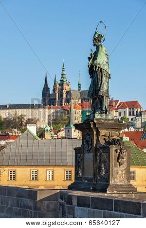 John of Nepomuk (or John Nepomucene) national saint of the Czech Republic statue on Charles Brigde at the site where the saint was thrown into Vltava with St. Vitus Cathedral in background in Prague