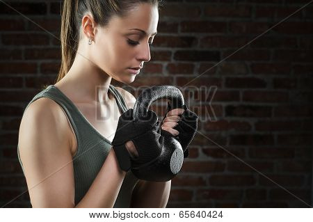 Young Fit Woman Lifting Kettle Bell On Dark Background