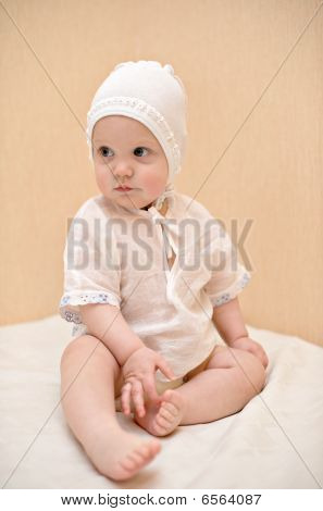 little kid dressed in white sits on the bed touching foot with his tiny finger