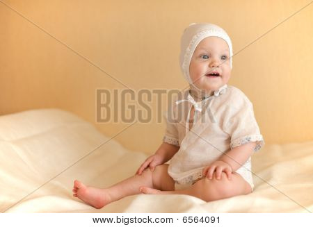 little kid dressed in white sits on the bed smiling with his head turned left
