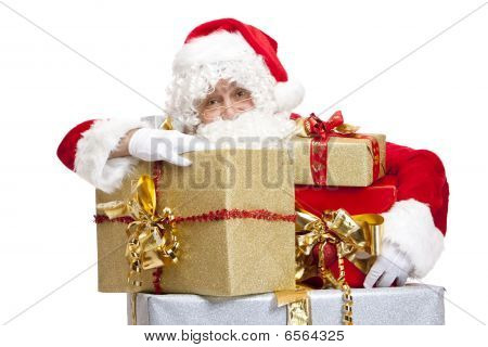 Old Male Santa Claus Is Leaning On A Stack Of Christmas Gift Boxes.