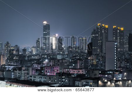 City night scene of Hong Kong with apartments and skyscrapers.