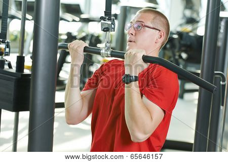 fitness man doing muscles exercises with training weight machine station in gym