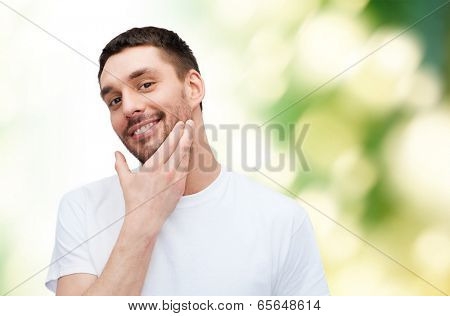 health and beauty concept - beautiful smiling man touching his face