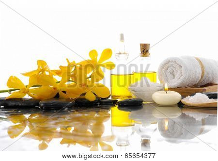 Spa feeling with Orchid and burn candles ,black stones, oil , on wet background