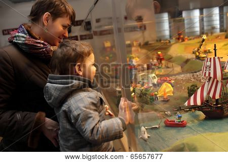 Family Looking At Toy Yacht