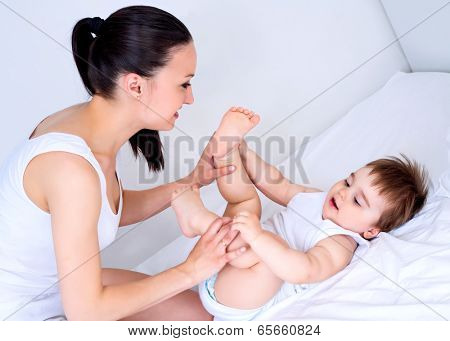 yong mother making massage to her two year old baby in bed at home