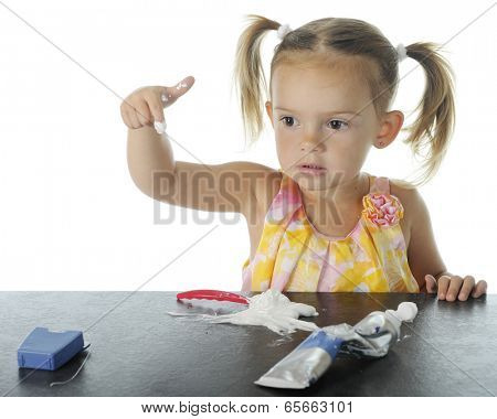 An adorable preschooler who has loaded her own toothbrush with toothpaste.  She's concerned about having it on the tip of her index finger.  On a white background.