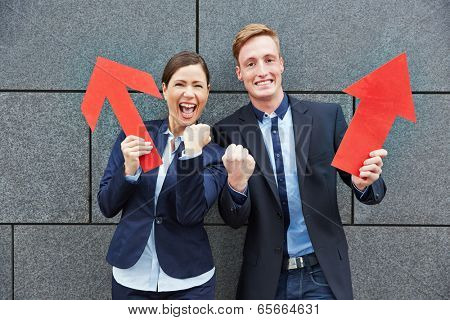 Two happy business people cheering with big red arrows pointing up