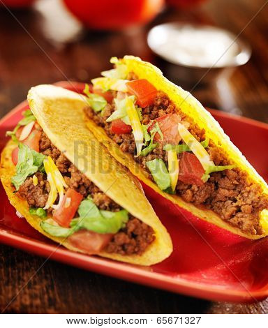 two beef tacos with cheese, lettuce and tomatoes