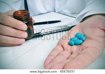 a doctor sitting in a desk with a pile of blue pills in his hand