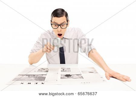 Man reading newspaper with magnifying glass isolated on white background