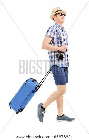 Young tourist carrying his luggage isolated on white background
