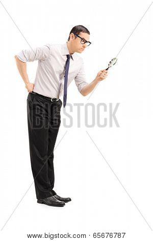 Serious man looking through a magnifying glass isolated on white background