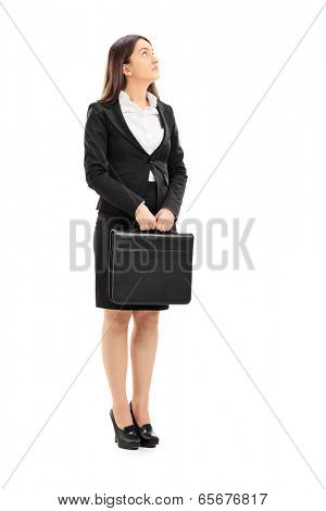 Full length portrait of a businesswoman holding a briefcase and looking up isolated on white background