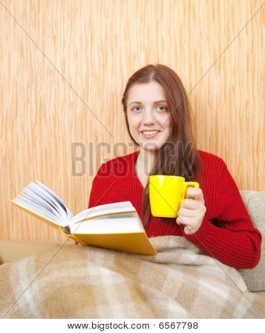 Woman On Sofa Reading And Drinking Coffee