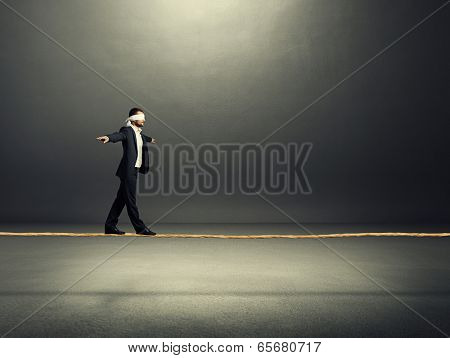businessman balancing on the rope over dark background