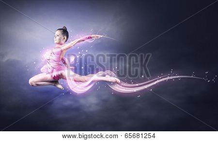 Cute girl gymnast in performance costume jumping high