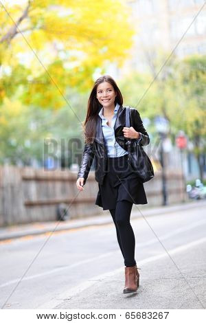Young urban professional woman in walking in city. Fashion girl living city lifestyle in leather jacket in autumn fall. Trendy modern female. Multiracial Asian Caucasian model.