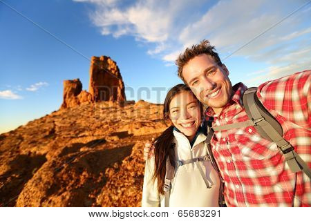 Selfie - Happy couple taking self portrait photo hiking. Two lovers or friends on hike smiling at camera outdoors mountains by Roque Nublo, Gran Canaria, Canary Islands, Spain.