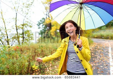 Autumn woman happy in rain running with umbrella. Female model looking up at clearing sky joyful on rainy fall day wearing yellow raincoat outside in nature forest by lake. Multi-ethnic Asian girl.
